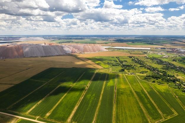 Горы продуктов для производства калийной соли и зеленое поле. соляные горы возле города солигорск. производство удобрений для земли. беларусь.