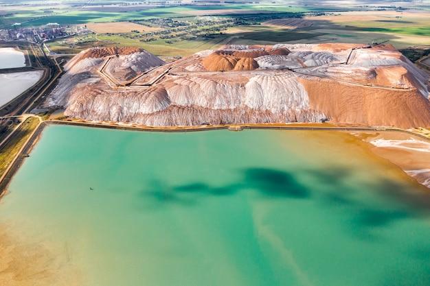 カリ塩と人工ターコイズ貯水池の生産のための製品の山。ソリゴルスク市の近くの塩の山。土地のための肥料の生産。ベラルーシ。