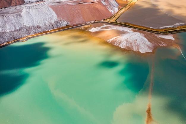 カリ塩と人工ターコイズ貯水池の生産のための製品の山。ソリゴルスク市の近くの塩山。