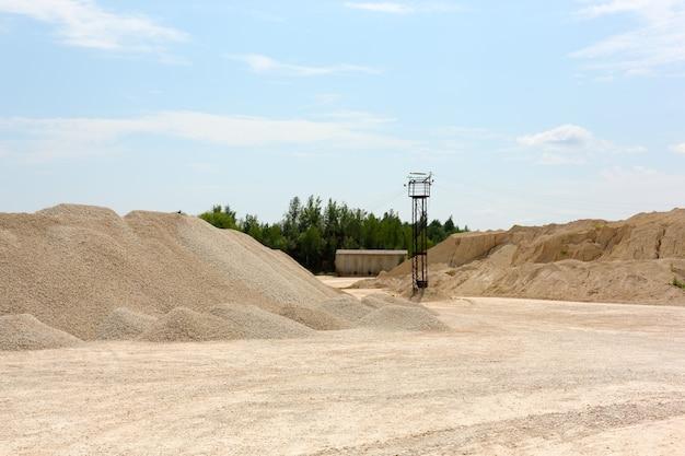 Горы из щебня и песка в летний день