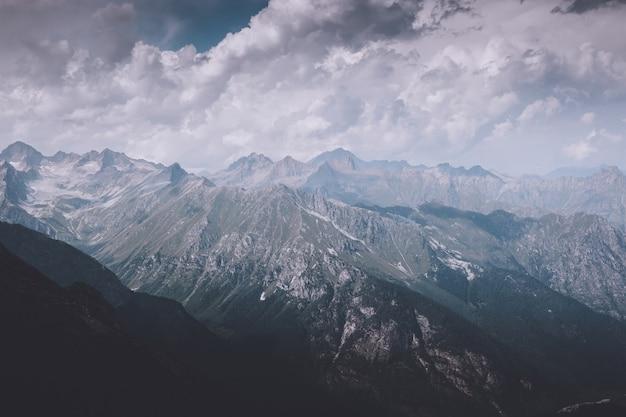 ロシア、コーカサス、ドンベイの国立公園で劇的な曇り空の山のシーン。夏の風景と晴れた日