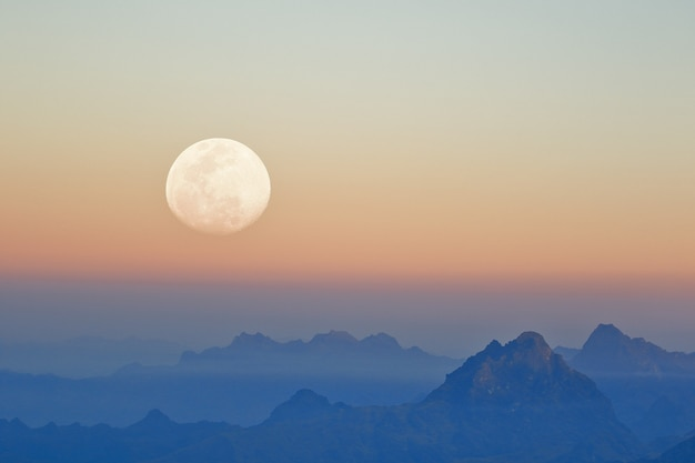 Mountains at sunset seen with the moon