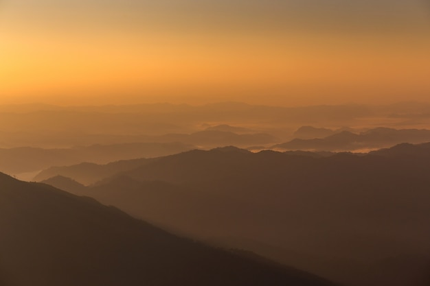 Mountains view sunrise orange horizon and clouds of background.