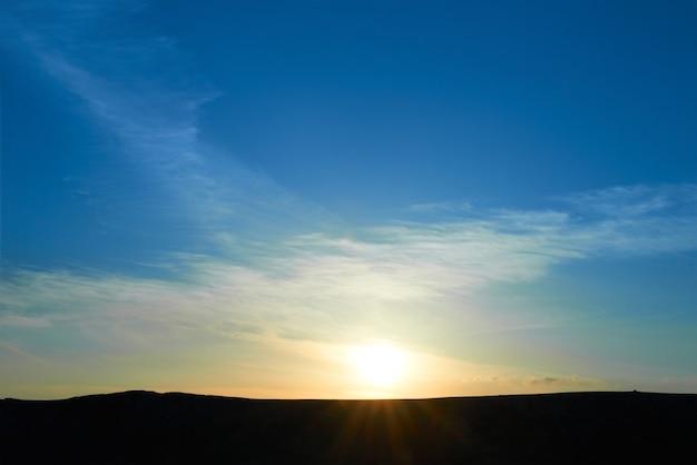 日没時にカラフルな青い空と山。太陽と雲