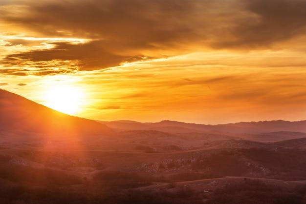 日没時に劇的なカラフルな空と山々