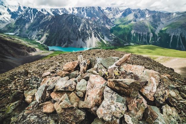 Тур на вершину горы с видом на живописную долину с большим красивым горным озером, окруженным гигантскими скалистыми хребтами и ледниками. сверху искусственная каменная свая. величественная первозданная природа высокогорья.