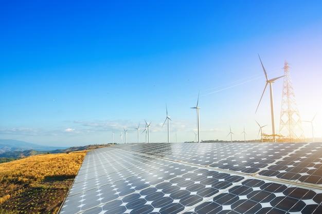 雲と青い空に対してmountanisの景色に対する風力発電機を備えたソーラーパネル