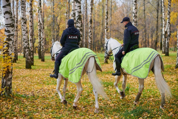 Mounted police in autumn city park, back view. all cops are bastards acronym, anarchism movement concept. two police officers on horseback patrol the park.