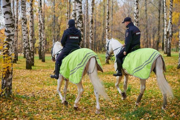 秋の都市公園に騎馬警官、背面図。馬に乗った2人のロシア人警官が公園をパトロールします。裏面にpoliceの刻印。