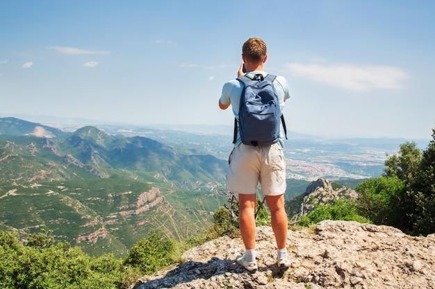 Путешествие человек с рюкзаком стоя сфотографировать на смартфон mountians солнечный день копия пространство