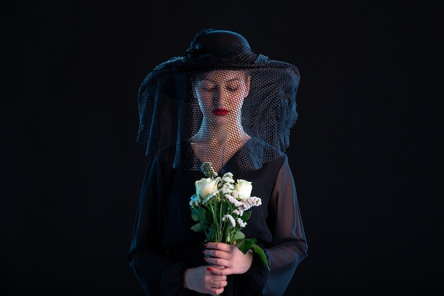 Mournful female dressed in all black with flowers on a black  funeral death sadness