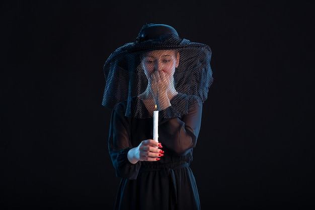 Mournful female dressed in black holding burning candle on black  death funeral