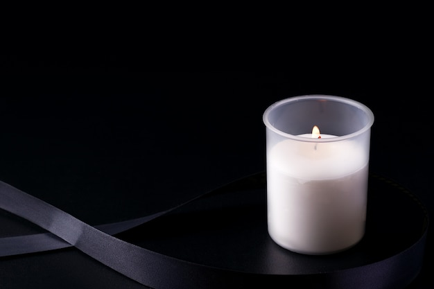 Траурная свеча рядом с лентой на черном