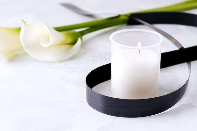 Траурная свеча на бетоне рядом с белыми цветами