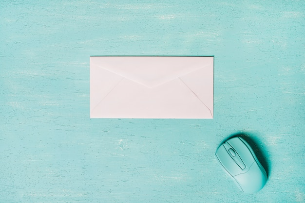 Mouse and white envelope on turquoise wooden textured background