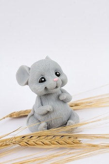 Mouse with ears of wheat sitting on a white