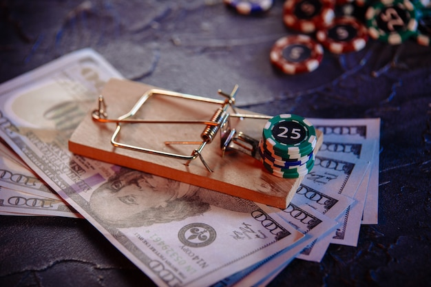 Mousetrap on dollar banknotes and casino chips on a grey wall