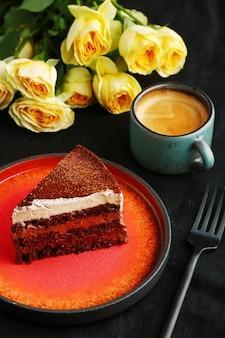Муссовый торт крупным планом на тарелке и чашке кофе и розы