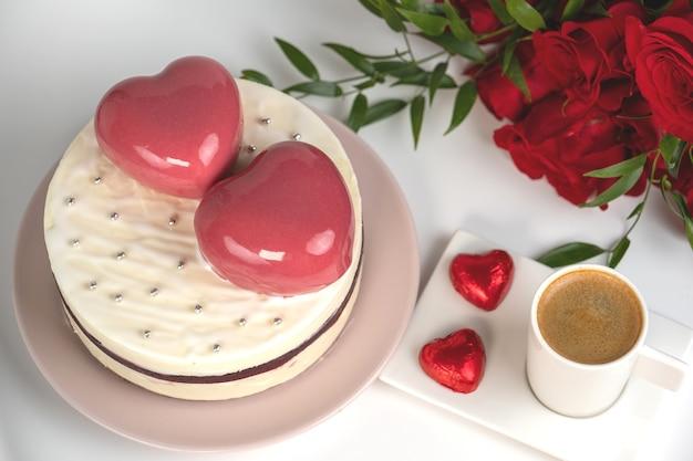 2つの大きなピンクのハートと白い釉薬のムースケーキ