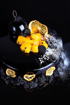 Mousse cake with black chocolate glaze with passion fruit and mango