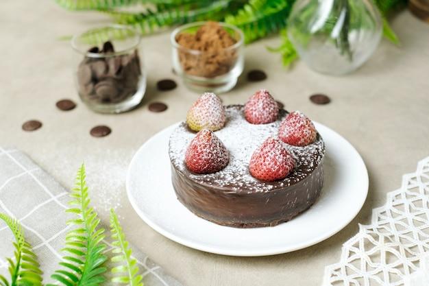 Муссовый шоколадный торт с клубникой и сахарной пудрой. набор на столик в кафе.