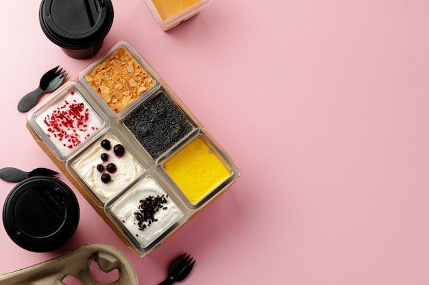 ピンクのテーブルにさまざまなトッピングが入った正方形のプラスチックの箱に入ったムースデザート