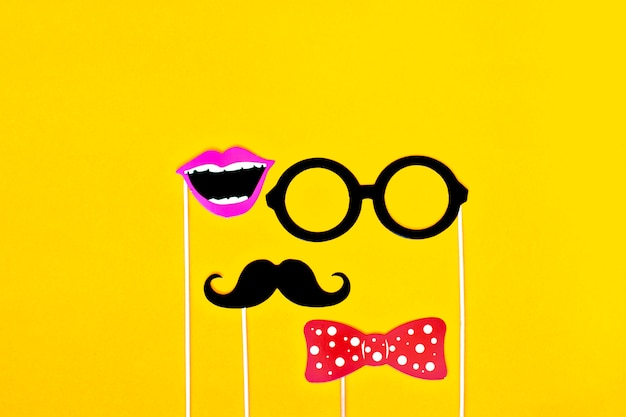 Moustache, tie, glasses, red mouth on wooden sticks against bright yellow background flat