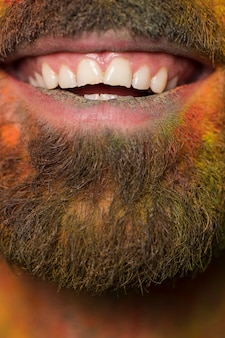 Mouth of toothy smiling bearded man with rainbow paint on face