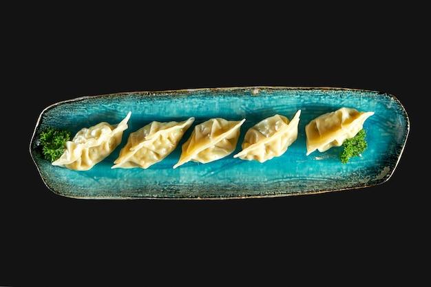 Аппетитная азиатская гёдза, фаршированная морепродуктами, подается на синей тарелке. японские цзяози или пельмени, изолированные на черном фоне. паназиатская кухня