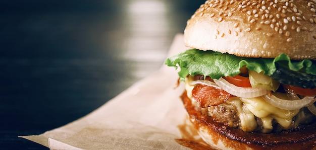 Аппетитный вкусный домашний бургер, из которого на деревянном столе нарезают говядину.