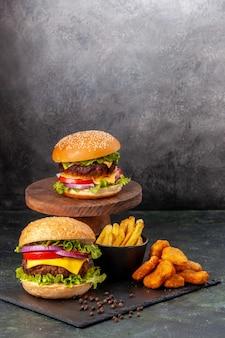 Deliziosi panini fritti fritti pepite di pollo su tavola nera patatine fritte pepe su superficie sfocata grigio scuro