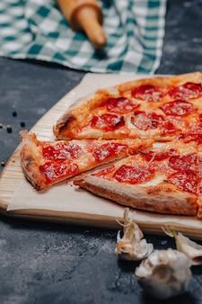 Аппетитная неаполитанская пицца на доске с различными ингредиентами, свободное место для текста