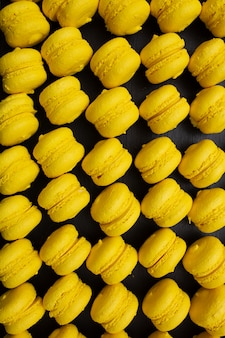 Mouth-watering yellow macaron maccarone on grey tray top view
