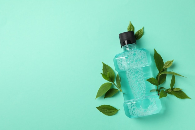 Mouthwash and leaves on mint background, space for text