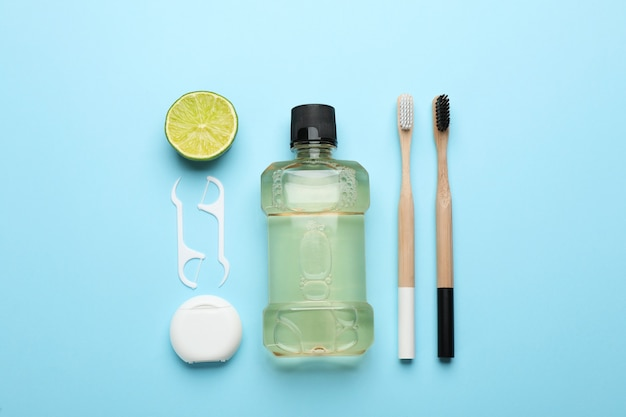 Mouthwash, toothbrushes, dental floss and lime on light blue background, flat lay