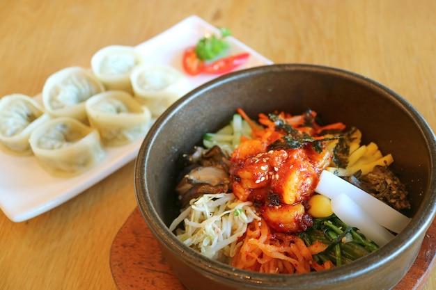 군침 도는 비빔밥 또는 배경에 흐릿한 만두 만두와 함께 한국의 혼합 밥 그릇