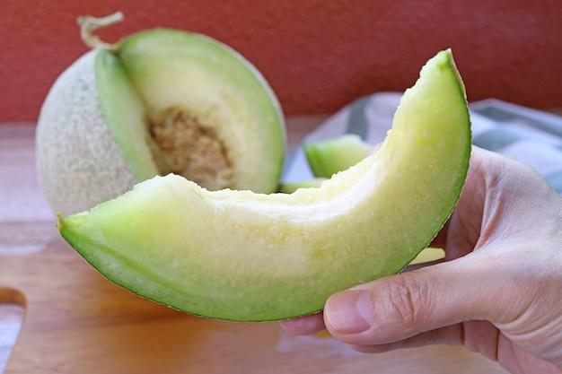 食欲をそそる新鮮な熟したジューシーなマスクメロンのスライスを手に、ぼやけた丸ごとの果物を背景に