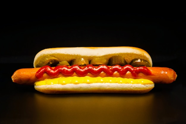 Mouthwatering long frankfurter in a wheat bun with chili pepper rings, ketchup and cheese sauce