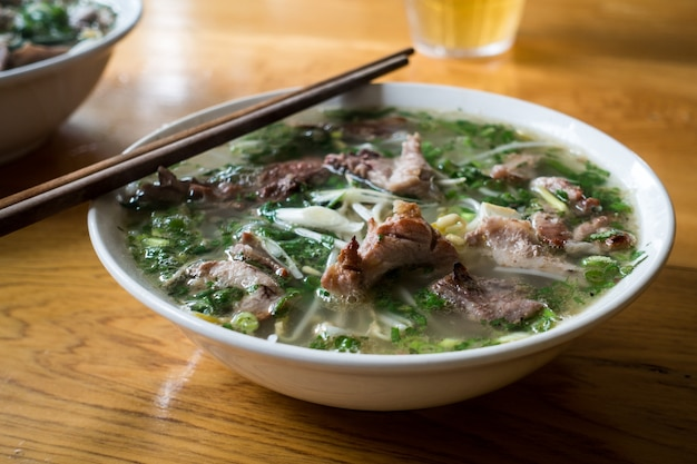 Mouthwatering vietnamese pho bo soup with chopsticks
