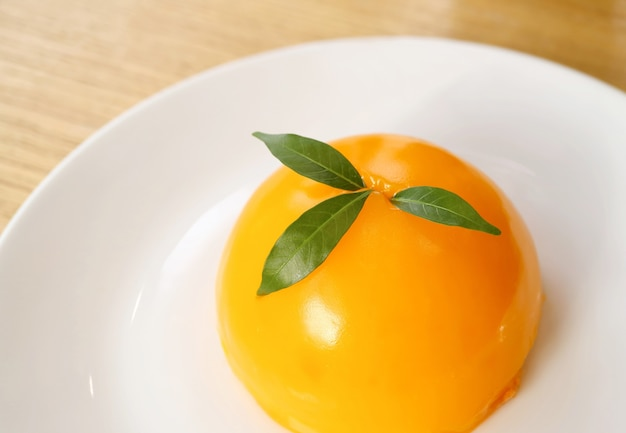 白いプレートに食欲をそそる鮮やかな色のマンダリンオレンジドームケーキ