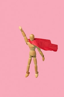Подвижный миниатюрный манекен-шарнир в красной накидке взлетает с поднятой рукой как супергерой или супермен
