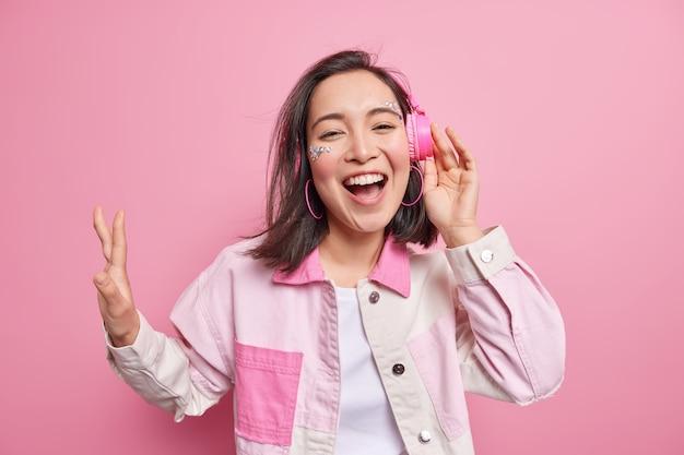 몸을 움직이고 긴장을 푸십시오. 긍정적 인 아시아 소녀는 좋아하는 재생 목록을 즐기고 무선 스테레오 헤드폰을 통해 재생 목록을 듣고 분홍색 벽 위에 고립 된 세련된 재킷을 입은 팔을 들어 올립니다.