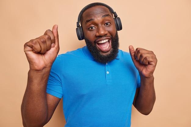 몸을 이동. 수염 난 남자가 무선 헤드폰을 끼고 춤을 추고 베이지색 스튜디오 벽에서 캐주얼하게 옷을 입고 최고의 음악 앱을 사용하여 좋아하는 노래를 즐깁니다.