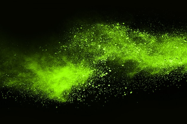 The movement of abstract dust explosion frozen green on black background.
