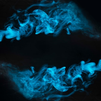 Movement of blue smoke on black background