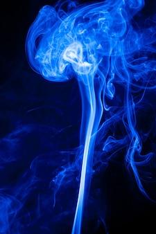 검은 배경에 운동 푸른 연기입니다.