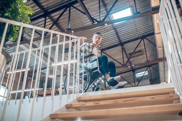 이동 제한. 휠체어를 탄 젊은 성인 외로운 남자는 실내로 내려가지 못하고 공포에 질려 계단을 보고 있다