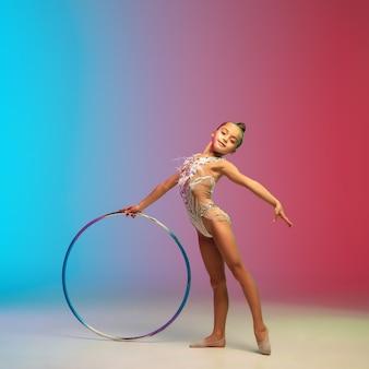 Движение. маленькая кавказская девочка, тренировка гимнастки, выступающая изолированно на градиентном сине-красном студийном фоне в неоне. грациозный и покладистый, крепкий ребенок. понятие спорта, движения, действия.