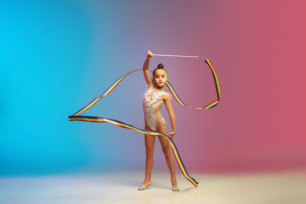 Movement. little caucasian girl, rhytmic gymnast training, performing isolated
