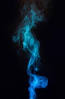 濃い黒の背景に透明な青い煙の動き